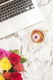 Feminine workplace concept. Freelance fashion comfortable femininity workspace in flat lay style with laptop, tea, flowers on whit. E marble background. Top view royalty free stock photography