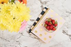 Feminine workplace concept. Freelance fashion comfortable femininity workspace in flat lay style with notebooks, strawberries, flo stock photo