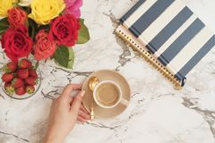 Feminine workplace concept. Freelance workspace in flat lay style with flowers. Woman hand holding cup of coffee. Blogger working. royalty free stock image