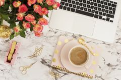 Feminine workplace concept. Freelance workspace in flat lay style with laptop, coffee, flowers, golden pineapple, notebook and pap. Er clips on white marble Royalty Free Stock Photography