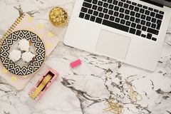 Feminine workplace concept. Freelance workspace in flat lay style with laptop, sweets, golden pineapple, notebook and paper clips stock photos