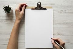 Feminine workspace with female hands, clipboard and sheet of paper, overhead. Top view stock image