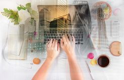 Feminine workspace, top view. Feminine workspace - laptop, coffee and phone with someones hands typing, top view, double exposure with modern cityscape Royalty Free Stock Photo