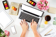 Feminine workspace, top view. Feminine workspace with laptop, tablet and phone with someones hands, top view Royalty Free Stock Image