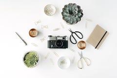 Feminini-Schreibtischarbeitsplatz mit saftiger, Retro- Kamera, Scheren, Tagebuch und goldenen Clipn auf weißem Hintergrund lizenzfreie stockfotos