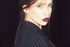 Femininity concept. Girl on strict confident face in black jacket, black background. Woman with stylish makeup and. Hairstyle. Lady with red lips looking at stock photography