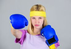 Femininity and strength balance. Woman boxing gloves enjoy workout. Girl learn how defend herself. Woman exercising with. Boxing gloves. Boxing sport concept stock photography