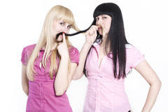 Feminism. Two girls trying to be like boys and made moustaches from their hair Stock Photography