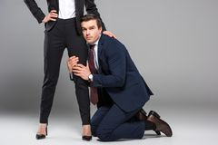Feminist businesswoman dominating over businessman. Isolated on grey stock images