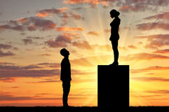 Feminists standing on a pedestal looking down at the man. Feminists silhouettes standing on a pedestal looking down at the man. Feminism concept Royalty Free Stock Image