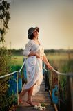 Feminity. The girl in a hat barefoot on the bridge stock photos