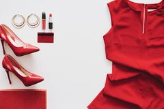 Feminity. Red dress, heels and cosmetics on white background royalty free stock image