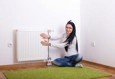 Femme à côté de radiateur chaud photos stock