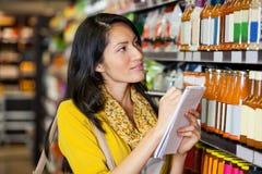 Femme à l'écriture de section d'épicerie en bloc-notes Images stock