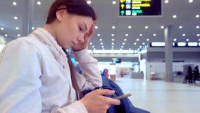 Femme à l'aéroport avec un téléphone portable dans des ses mains attendant son vol, vue de côté banque de vidéos