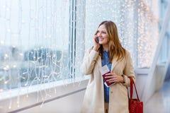 Femme à l'aéroport international parlant par l'intermédiaire du téléphone portable Photos stock
