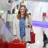 Femme à l'aéroport international, sur l'escalator sur le terminal d'arrivée Photos stock