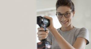 Femme à l'aide d'un foret et travaillant dans sa nouvelle maison image stock