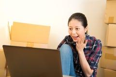 Femme à l'aide d'un ordinateur portable excité photographie stock libre de droits