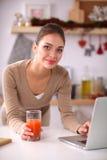 Femme à l'aide d'un ordinateur portable tout en buvant du jus dans sa cuisine Image stock