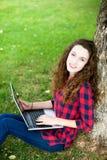 Femme à l'aide d'un ordinateur portatif sous un arbre Image stock