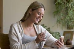 Femme à l'aide d'un smartphone dans sa maison Image libre de droits
