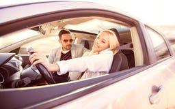 Femme à l'aide d'un smartphone tout en conduisant une voiture Photographie stock libre de droits
