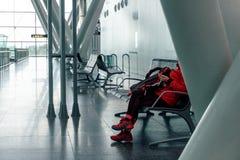 Femme à l'aide d'un téléphone portable à l'aéroport et attendant son vol photo stock