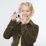 Femme à l'aide de l'appareil photo numérique. Photographie stock libre de droits