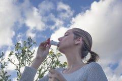 Femme à l'aide de l'inhalateur pour traiter l'asthme allergique Photo stock