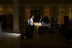 Femme à l'aide de l'ordinateur dans le bureau foncé photo libre de droits