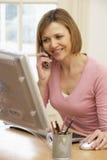 Femme à l'aide de l'ordinateur et parlant au téléphone Photo stock