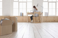 Femme à l'aide de l'ordinateur portable au bureau en appartement de grenier Photographie stock