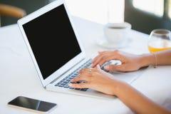 Femme à l'aide de l'ordinateur portable dans un restaurant Photos stock