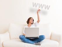 Femme à l'aide de l'ordinateur portable et buvant d'une tasse Photo libre de droits