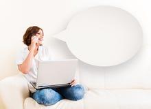 Femme à l'aide de l'ordinateur portable et d'un téléphone sur le sofa Photographie stock