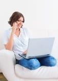 Femme à l'aide de l'ordinateur portable et d'un téléphone sur le sofa Photos stock