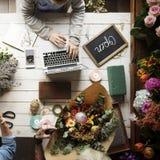 Femme à l'aide de l'ordinateur portable recherchant sur l'Internet pour faire des emplettes usines de fleurs Image stock