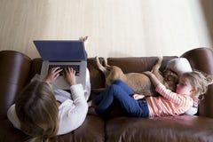 Femme à l'aide de l'ordinateur portable tandis que la fille et le chien dorment Photos stock
