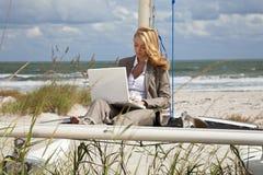 Femme à l'aide de l'ordinateur portatif sur le bateau à la plage Photographie stock