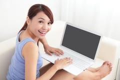 Femme à l'aide de l'ordinateur portatif sur le sofa Photographie stock