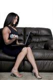 Femme à l'aide de l'ordinateur portatif tout en établissant images stock