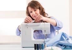 Femme à l'aide de la machine à coudre photos stock