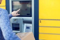 Femme à l'aide de la machine ou de la serrure terminale automatisée de courrier de service d'individu image libre de droits