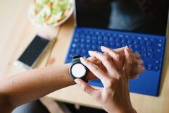 Femme à l'aide de la montre intelligente et travaillant à la maison sur l'ordinateur portable photographie stock