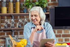Femme à l'aide de la Tablette de Digital dans la cuisine Photos stock