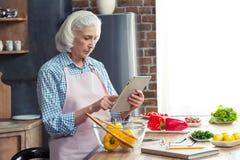 Femme à l'aide de la Tablette de Digital dans la cuisine Image stock