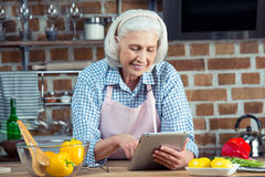 Femme à l'aide de la Tablette de Digital dans la cuisine Photo libre de droits