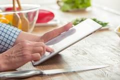 Femme à l'aide de la Tablette de Digital dans la cuisine Photos libres de droits