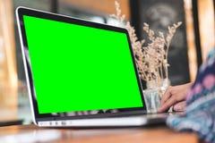 Femme à l'aide de l'ordinateur portable avec l'écran vert vide sur la table en bois dans le bureau Photographie stock libre de droits